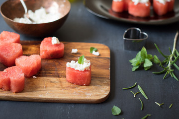 Macro shot of heart-shaped watermelon with feta cheese and mint leaf. Selective focus