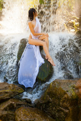 Naked girl sitting on a rock by a waterfall.