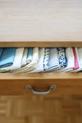 Tea towels neatly arranged in a drawer of dining table