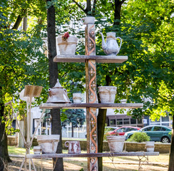 Wooden shelves in the form of a Christmas tree on which there is a ceramic teapot, jug, plate, bowl in the park among the trees