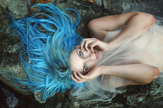 Beautiful water nymph posing on rocks