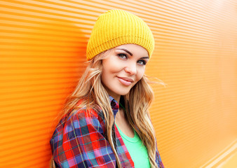 Portrait of pretty blonde woman in colorful clothes outdoors