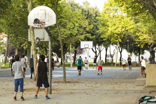 Unrecognizable basketball players on numerous courts on a nice sunny day in a park