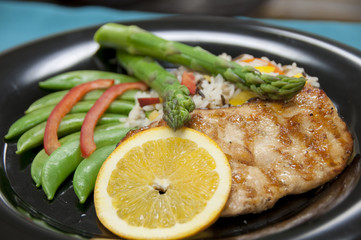 healthy food with grilled chicken, asparagus, lemon slice, snap peas, and rice.