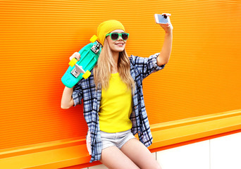 Fashion and technology concept - stylish young girl in colorful