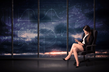 Businesswoman holding tablet in office room with graph charts on