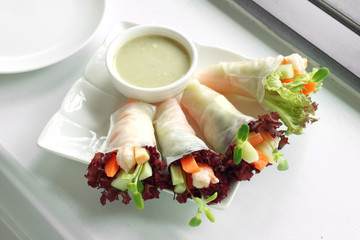 vietnamese salad roll and sauce in white ceramic dish