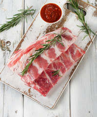 Raw ribs on a wooden cutting board.