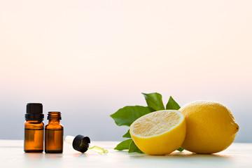 Lemon essential oils in bottles with lemon