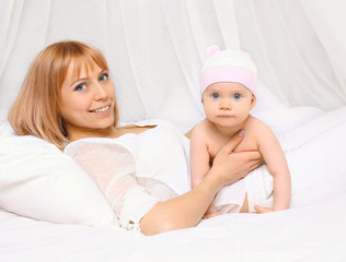 Portrait of happy mother lying with baby together on the bed at