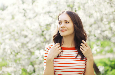 Portrait of happy beautiful young woman in flowering spring gard