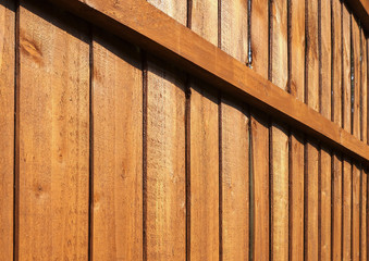 Wooden garden fence close up with vertical panels and horizontal