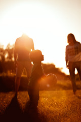 Happy family in park- family concept. Shot of little boy playing football on background of his parents. Mather, father and son in park or forest on sunset.