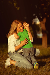 Mother hugging her son with love in park. Image about mother love. Beautiful young mother and her little son in garden or in park.