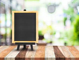 Blackboard menu with easel on wooden table with blur coffee shop