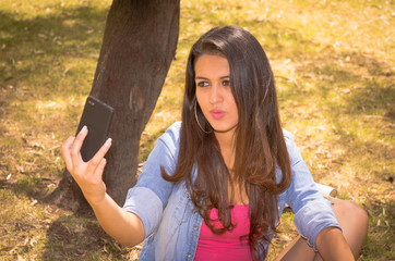 Young attractive brunette girl with cell phone in the park