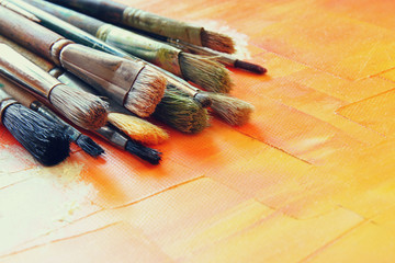 top view of set of used paint brushes over wooden table