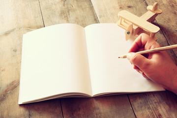 open blank notebook and woman hands next to toy aeroplane on wooden table