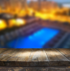 wood board table in front of rich hotel pool at night