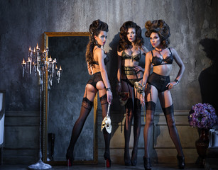 Three girls in lingerie, masks, standing near a vintage mirror