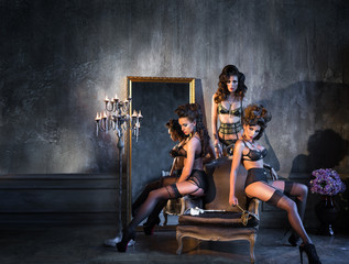 Three girls in lingerie sitting near the old mirror