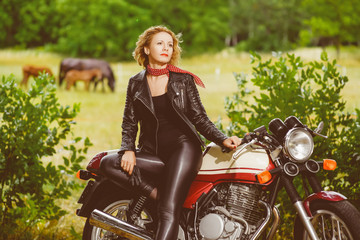 Biker girl in leather jacket on a motorcycle over the background