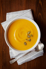 Fresh autumn pumpkin cream soup in bowl, dietary vegetable soup, top view