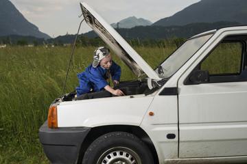 Bambino meccanico al lavoro su autovettura