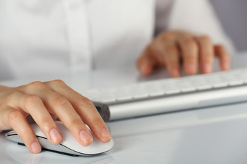 Female hands typing on keyboard and holding computer mouse on light background