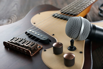 Electric guitar with microphone on wooden table close up