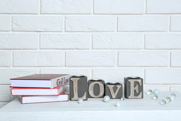 Books with word Love on brick wall background