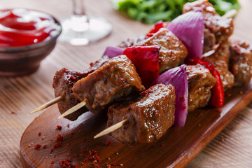 skewers kebab of meat with red sauce on the board