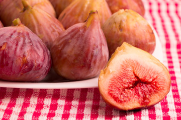 Group of figs in a white plate, with one cut fig on red tablecloth
