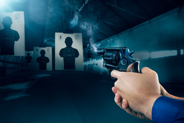Police officer firing a gun at a shooting range / dramatic light