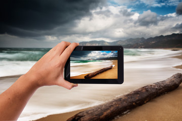 Tablet in hand photo shooting bad wheather on a beach in winter - these are all photos made by me, that you separately can find on my fotolia portfolio.