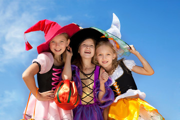 Three Cute Little Witches Standing with Bags