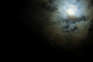 Full Moon shines through the clouds scary
