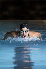 female swimmer swimming butterfly stroke.