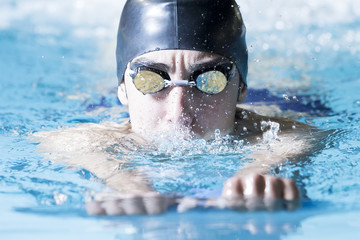 young male swimmer swimming with a swim board.