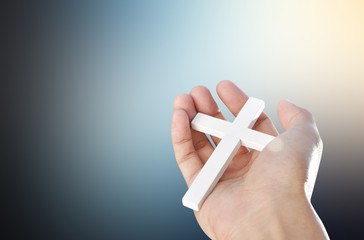 Hand and cross on dark light  background , concept design