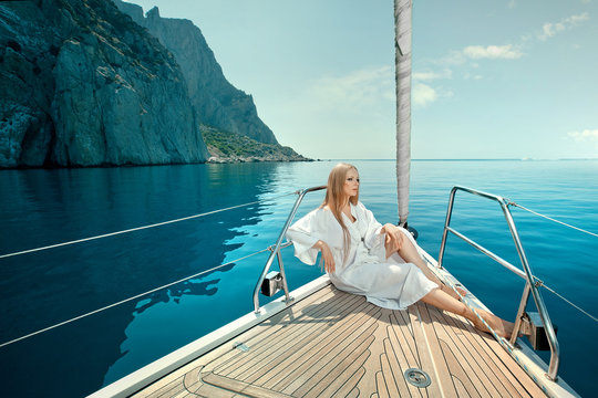 sexy young woman lies on yacht bow in sunglasses and dressing gown