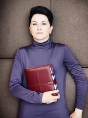 Sad businesswoman lies with personal organizer handheld on brown sofa