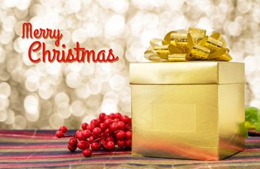 Merry Christmas word with Gold present box and ribbon on table w