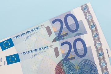Two twenty euro notes on light blue background