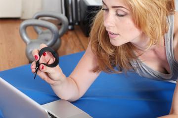 Frau synchronisiert Ihre Trainingsuhr mit dem Laptop