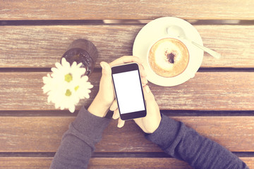 Girl with blank cell phone and cup of coffee