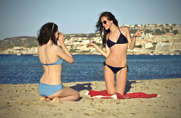 Two girls taking pictures at the seaside