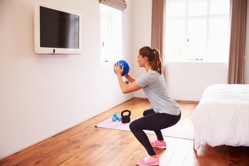 Woman With Ball Working Out To Fitness DVD On TV In Bedroom