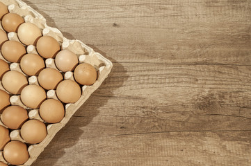 Close up eggs in carton package on a wooden table for baking