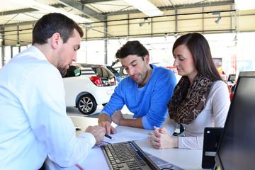 Verkaufsgespräch und Vertragsunterzeichnung im Autohaus - junges Paar kauf Auto - Verkäufer mit Kunden im Showrrom